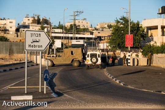 Israeli soldiers shut down the entrance to the West Bank city of Hebron, seen on June 15, 2014. A complete closure was put on the city after three Israeli teenagers went missing near a West Bank settlement. The three, all students at a Jewish seminary, went missing late on June 12 as they were hitchhiking between Bethlehem and Hebron and are believed to have been kidnapped. (Photo by Yotam Ronen/Activestills.org)