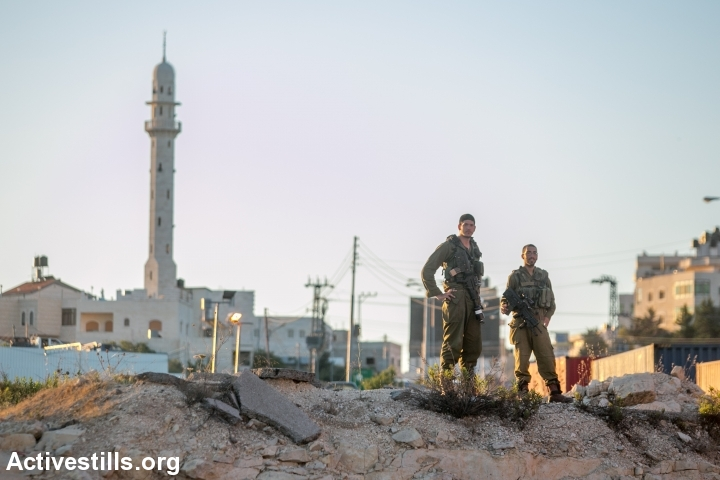 Israeli soldiers stationed at the entrance to the West Bank city of Hebron, seen on June 15, 2014. A complete closure was put on the city after three Israeli teenagers went missing near a West Bank settlement. The three, all students at a Jewish seminary, went missing late on June 12 as they were hitchhiking between Bethlehem and Hebron and are believed to have been kidnapped. (Photo by Yotam Ronen/Activestills.org)