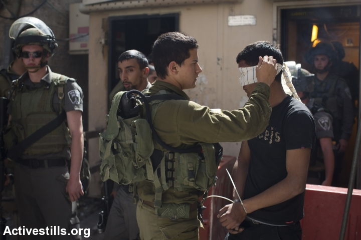 Israeli soldiers blindfold and arrest a young Palestinian man in Hebron. The Israeli army rounded up hundreds of Hamas members, including journalists and parliament members, while searching for three kidnapped Israeli teens. (photo: Activestills.org)