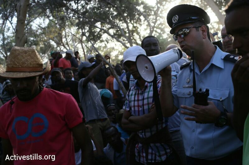 A police officer warns asylum seekers that they must get onto buses back to Holot, June 29, 2014. (Photo: Oren Ziv/Activestills.org)