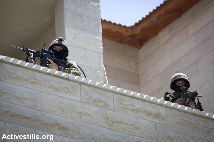 Israeli soldiers take part in a search operation for three Israeli teenagers believed kidnapped by Palestinian militants, on June 18, 2014, in the West Bank town of Halhul. Israel stepped up efforts to crush Hamas in the West Bank as the hunt for three Israeli teenagers went on. (Photo by Oren Ziv/Activestills.org)