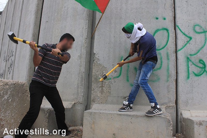 Palestinian activists try to destroy parts of the separation wall during the 'Return March near Tulkarem, West Bank, May 31, 2014. The marchers attempted to cross the barrier while chanting the names of their destroyed villages and towns located inside Israel. (photo: Activestills)