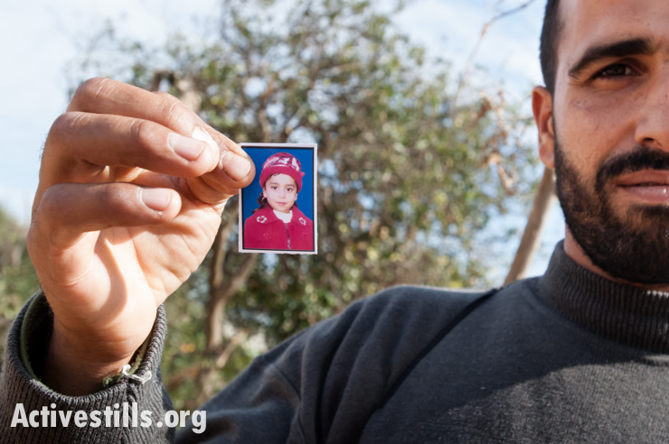 """Citrus farmer Yusuf Jilal Arafat holds a photo of his 5-year-old daughter Runan, who was killed when 10 Israeli missiles struck their mostly agricultural area in the Al Zeitoun neighborhood of Gaza City, December 2, 2012 during the offensive known as """"Operation Pillar of Cloud""""."""