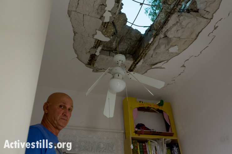 An Israeli resident looks at damage from a rocket from Gaza that struck his home in a kibbutz near border with the Gaza Strip on Wednesday, July 9, 2014.