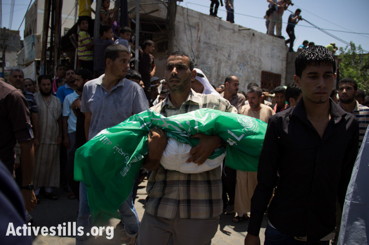 A mourner carries the body of a child among 24 members of the Abu Jamea family, who were killed the previous day during an Israeli attack over the Bani Suhaila neighborhood of Khan Younis, Gaza Strip.