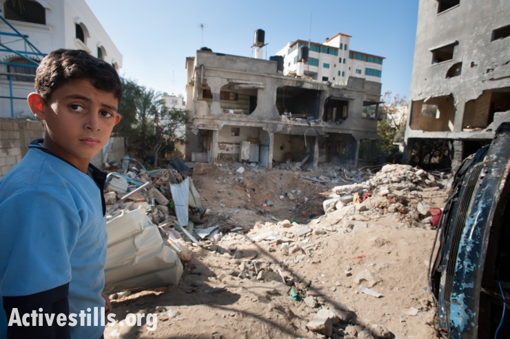 A child stands  amid the rubble of the Al Dalu family home, Gaza City, December 3, 2012. Ten members of the Al Dalu family were killed, as well as two neighbors, by an Israeli air strike on their three-story home on November 18, 2012. Four of those killed were children, and four were women.