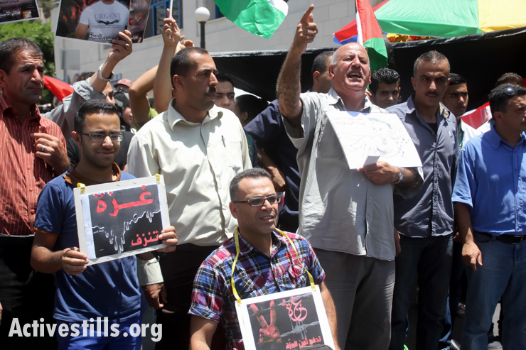"Palestinians hold signs reading ""Gaza is bleeding"" during a solidarity demonstration in the city center of Nablus, West Bank, July 09, 2014."