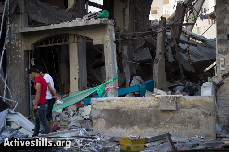 Palestinians walk among the ruins of the Abu Leila family house which was destroyed by an Israeli air strike in the Al Sheikh Radwan neighborhood of Gaza City early the morning of July 11, 2014.