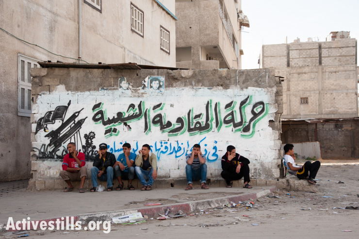 """Gaza youth sit in front of a spray-painted mural depicting rockets with the slogan, """"Popular Resistance Movement"""", Gaza City, December 2, 2012."""