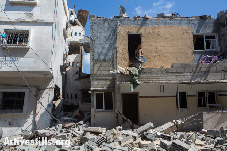 Palestinians inspect the destroyed house of the Eshtawi family in Az-Zeitiun area, Gaza City, July 14, 2014. The attack left 27 people homeless.