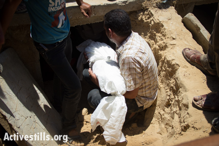 Mourners bury the body of a child among 24 members of the Abu Jamea family, who were killed the previous day during an Israeli attack over the Bani Suhaila neighborhood of Khan Younis, Gaza Strip.