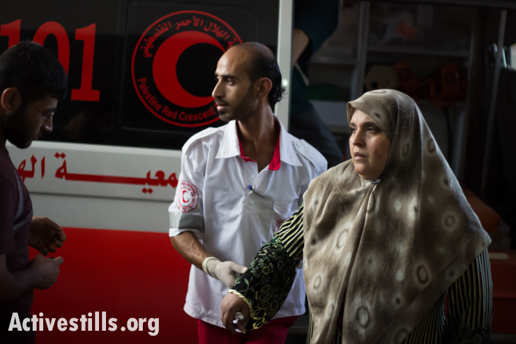 Palestinian medical staff care for those injured in Israeli air strikes as they arrive at Al Shifa Hospital in Gaza City on July 8, 2014.