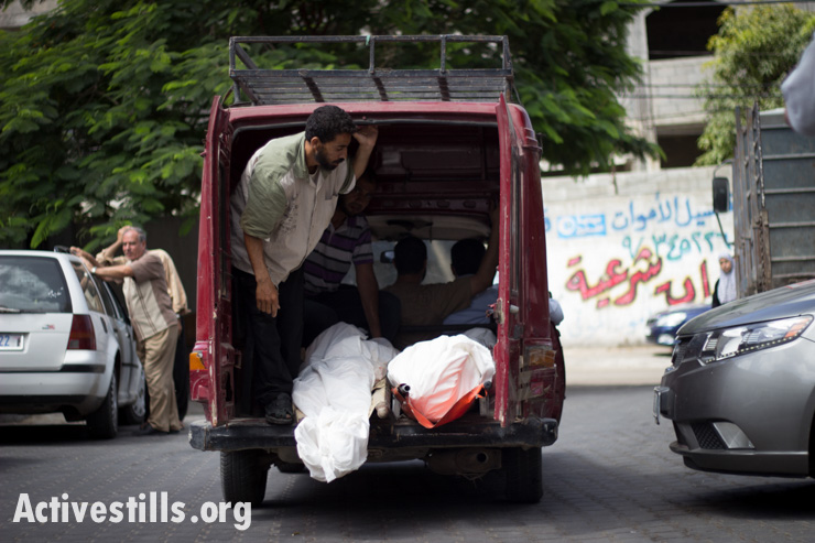 Members of the al-Batsh family are taken from Al Shifa Hosptial for their funeral, Gaza City, July 13, 2014.