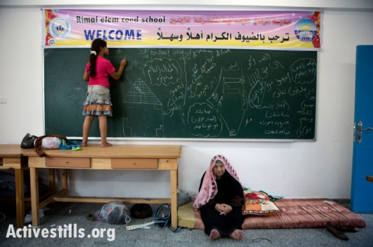 A Palestinian girl from the Al-Tom family draws on a chalk board at UNRWA's Remal Elementary School in Gaza City which is used as a temporary shelter for Palestinians fleeing the northern Gaza Strip,  July 13, 2014. (photo: ActiveStills)