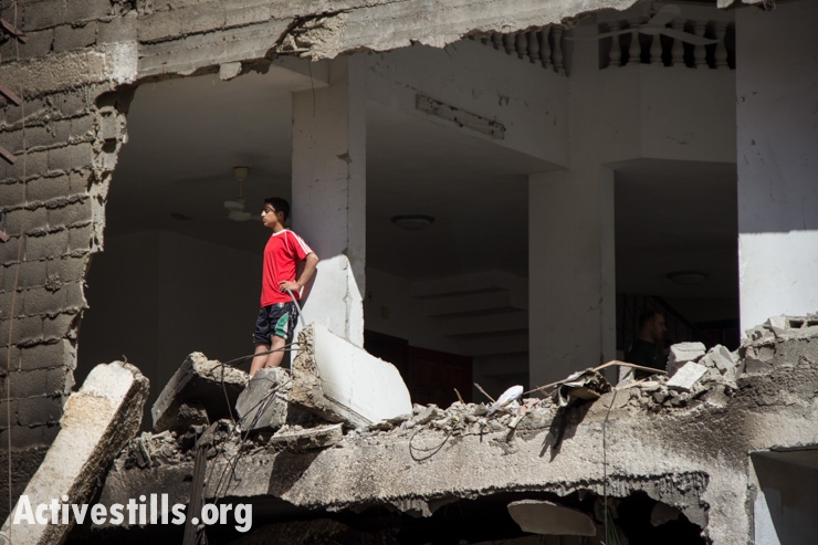 A Palestinian looks out from a building destroyed by Israeli attacks in Gaza City, July 14, 2014.