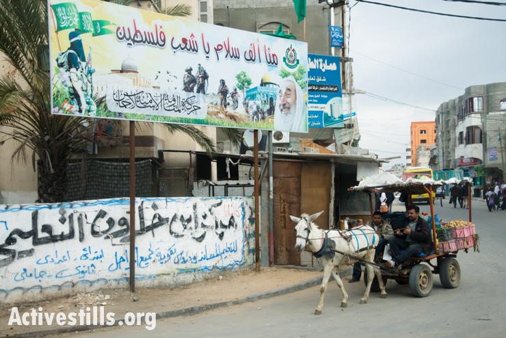 A donkey cart passes a Hamas billboard in Gaza City, January 26, 2014.