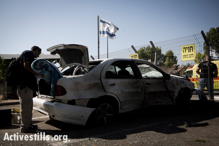 An Israeli man in Sderot looks at his car that was hit by a rocket fired from the Gaza Strip, July 10, 2014.