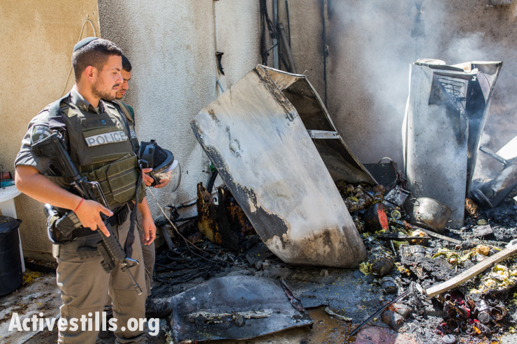 Israeli border policemen stand near a house in Kfar Aza, Israel, damaged by a rocket launched from the Gaza Strip on July 14, 2014.