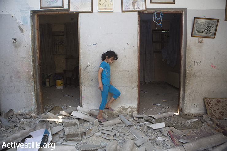 A child of Diab Bakr is seen amidst the rubble of her home, which was destroyed the previous night by Israeli missiles, in As-Shati refugee camp, Gaza City, July 22, 2014. Another home of the extended Bakr family was also destroyed and one other damaged. Another member of the family, Hassan Khader Bakr, was killed in an attack in the street. (Anne Paq/Activestills.org)