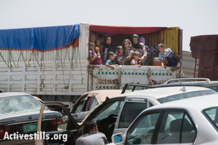 Internally displaced people ride in the back of a truck outside the Khazer Checkpoint between Nineveh and Erbil Provinces in Iraqi Kurdistan, July 9, 2014. According the the BBC, more than a million people have fled their homes as a result of the fighting in Iraq in recent months.