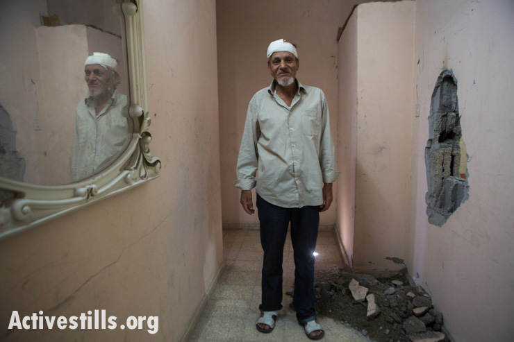 """Majeed Al-Zeem, age 52, stands next to an hole from a missile launched by a drone which caused his head injury, Gaza City, July 14, 2014. The missile was launched by the Israeli military to warn the family of an impending airstrike on the house next door, an example of the so-called """"knock on roof"""" tactic."""