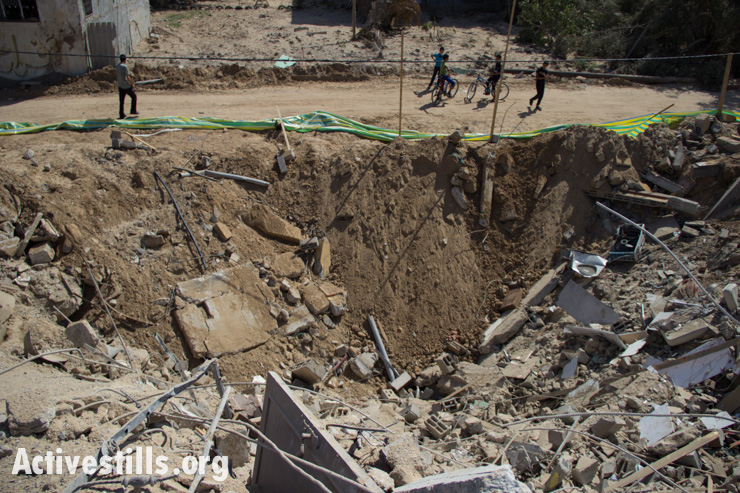 Palestinian children ride bicycles past a bomb crater in Gaza City, July 14, 2014.
