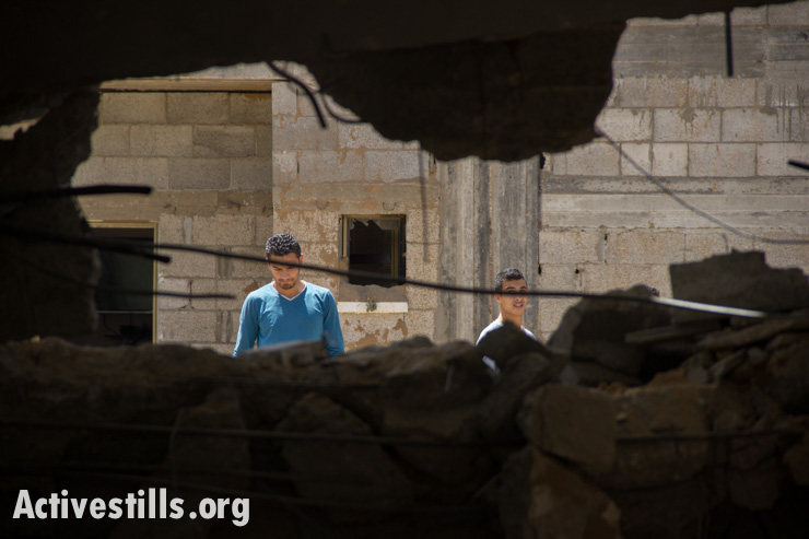 Palestinians inspect the damage of destroyed homes, Gaza City, July 14, 2014.