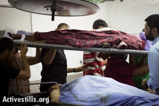 Bodies are carried from the morgue of Al Shifa Hosptial, Gaza City, July 13, 2014.