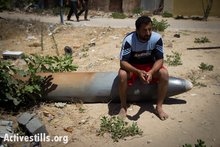 Hussam Shamdi sits on an missile which did not explode from the air strike which destroyed his home the day before, in Tel al-Hawa neighbourhood of Gaza City, July 14, 2014. (photo: ActiveStills)