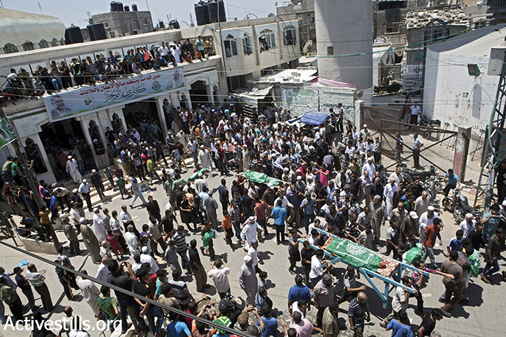 Palestinian mourners carry the bodies of the members of the Abu Jame' family out of the mosque. Certain bodies are carried in cardboard boxes as they were torn to pieces by the shelling.