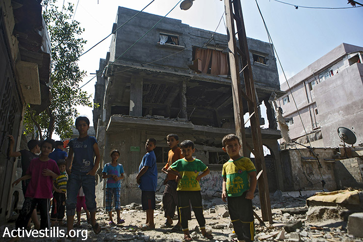 Members from the extended Bakr family stand outside their destroyed houses in As-Shati refugee camp, Gaza City, July 22, 2014. Their cousins, who live in the same area, lost four children, Ahed (10), Zacharia (10) and Mohamed (9) when they were targeted by Israeli attacks while playing on the beach on July 16, 2014. (Anne Paq/Activestills.org)
