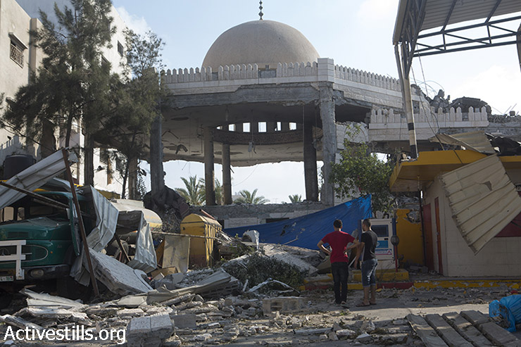 Palestinians inspect the rubble of the Al Aqsa Martyrs mosque in Gaza City, destroyed by an overnight Israeli strike, July 22, 2014. (Anne Paq/Activestills.org)