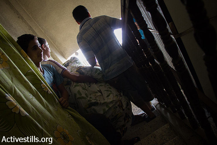 Residents of the Hashem building evacuate their apartments after the building was heavily damaged by an Israeli air strike over Al-Sabbra neighborhood. (Basel Yazouri/Activestills.org)