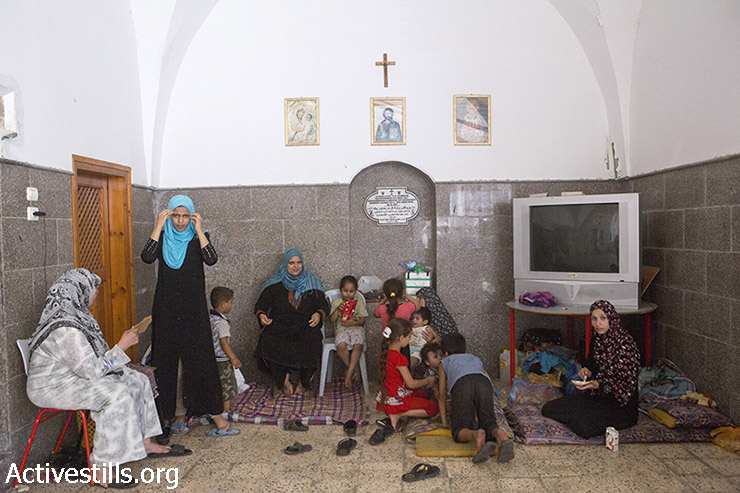 Palestinians sit inside central Gaza City's Church of St. Porphyrius, where they find refuge, July 22, 2014. UNRWA states that they are sheltering more than 110,000 displaced Palestinians in UNRWA schools, but the total number is much higher. (Anne Paq/Activestills.org)