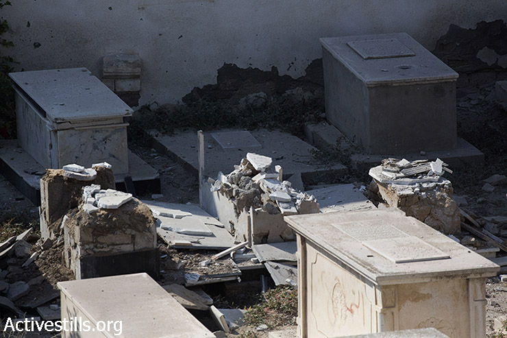 A view on the damages caused by an Israeli attack on the cemetery next to Gaza City's Church of St. Porphyrius where scores of Palestinians have taken refuge, July 22, 2014. Israeli attacks have killed 620 Palestinians and injured more than 3,700 in the current offensive, most of them civilians. (Anne Paq/Activestills.org)