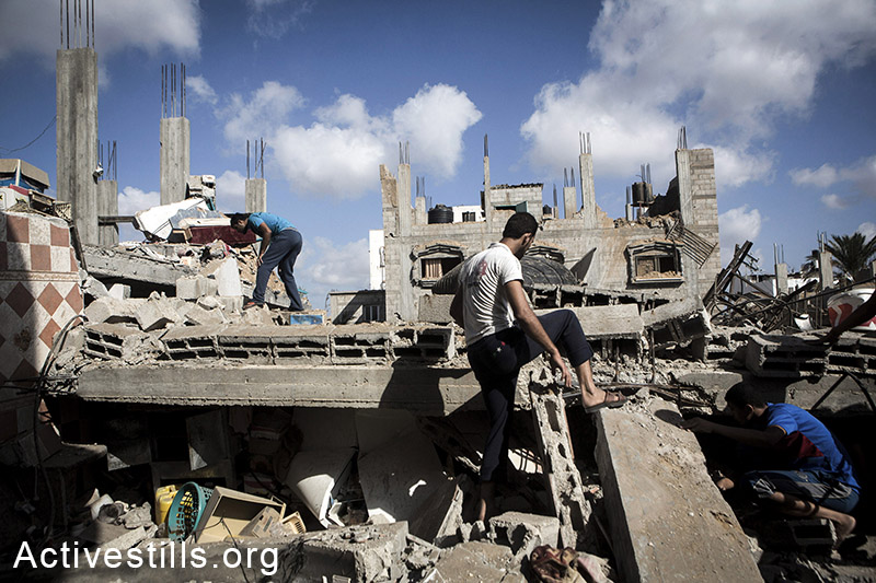 Palestinians look for injured or dead bodies under the rubble of the home of Abu Teir family which was bombed duri,h an Israeli attack, in Abasan village, East of Khan Yunis, July 27, 2014. During the ceasefire on 26 July, many Palestinians went back to Abasan to inspect the damages together with medics who attempted to rescue injured or collect bodies.  Israeli attacks have killed more than 1,000 Palestinians and injured around 5,000 in the current offensive. (Anne Paq/Activestills.org)