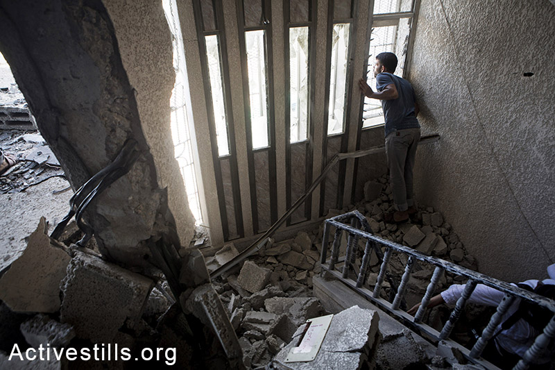 Palestinians inspect damages in Abasan village, East of Khan Yunis, July 27, 2014. During the ceasefire on 26 July, many Palestinians went back to Abasan to inspect the damages together with medics who attempted to rescue injured or collect bodies.  Israeli attacks have killed more than 1,000 Palestinians and injured around 5,000 in the current offensive.  (Anne Paq/Activestills.org)