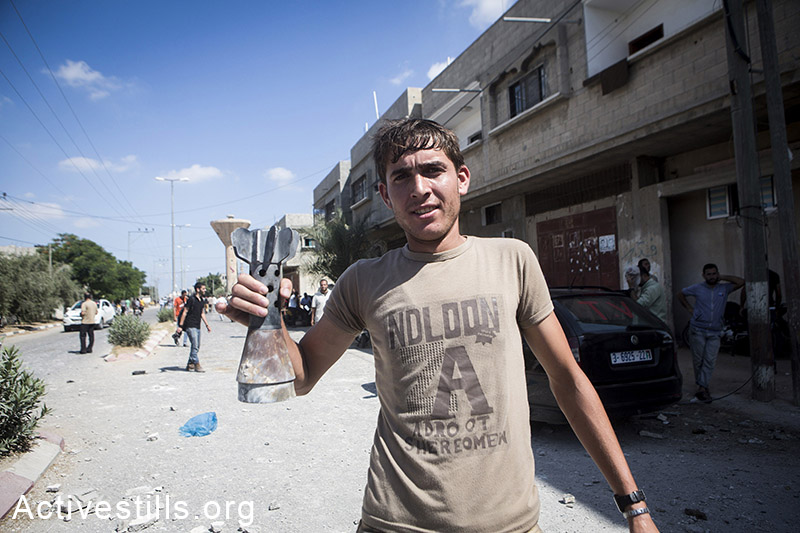 A Palestinian shows pieces of Israeli weapon in Abasan village at the entrance of another village Khuza'a, East of Khan Yunis, July 27, 2014. During the ceasefire on 26 July, many Palestinians went back to Abasan to inspect the damages together with medics who attempted to rescue injured or collect bodies. Residents of adjacent Khuza'a could not enter, as Israeli soldiers fired warning shots. Israeli attacks have killed more than 1,000 Palestinians and injured around 5,000 in the current offensive. (Anne Paq/Activestills.org)