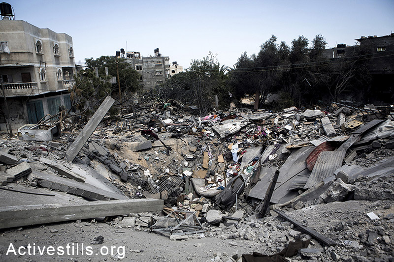A huge crater is seen in place of a home that was bombed during an Israeli attack, Bani Suheila, East of Khan Yunis, July 27, 2014. (Anne Paq/Activestills.org)