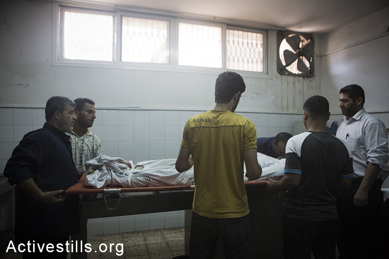 Relatives mourn on family members at the Al Shifa hospital as more bodies arrive from the Shejaiya area, July 20, 2014. (Basel Yazouri/Activestills.org)