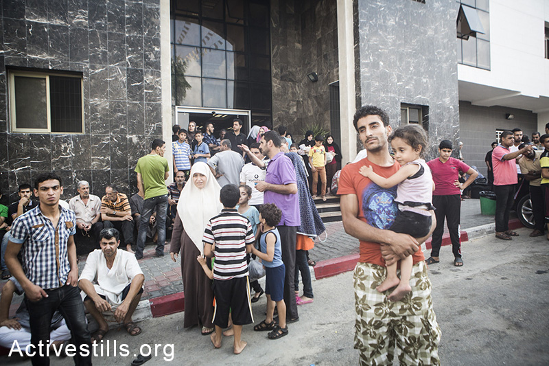 Gazans stand outside Al Shifa hospital, July 20, 2014.  (Basel Yazouri/Activestills.org)