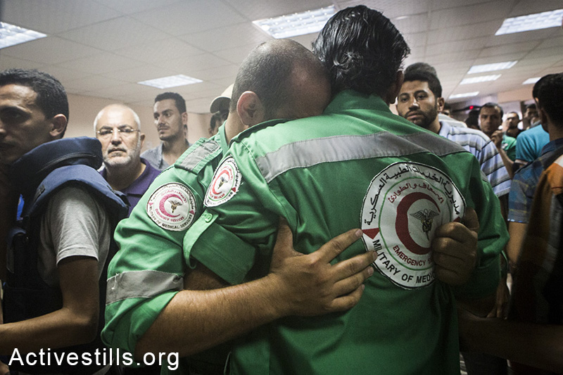 Medics at the Al-Shifa hospital mourn their colleague targeted and killed in Shejaiya neighbourhood earlier today, July 20, 2014. (Anne Paq/Activestills.org)