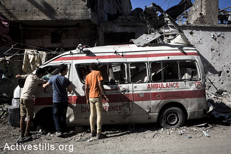 Palestinians inspect damage to a destroyed ambulance in Shujaiyeh, a neighborhood in the east of Gaza City, during the July 27 ceasefire. (photo: Activestills.org)
