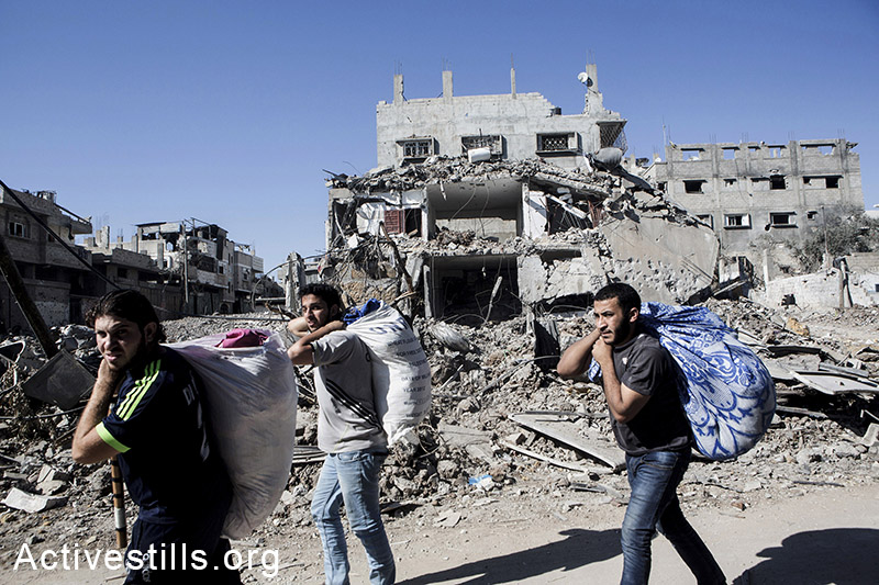 Palestinians walk out with belongings in Shujaiyeh, a neighborhood in the east of Gaza City, during a ceasefire, July 27, 2014. During the ceasefire on 26 July, many Palestinians went back to Shujaiyeh to inspect the damages together with medics who attempted to rescue injured or collect bodies. Dozens of bodies were collected but many remain as Palestinians do not have all the necessary equipment to dig. Israeli attacks turned the neighborhood into a scene of utter devastation, with entire buildings flattened and thousands forced to flee.  Israeli attacks have killed more than 1,000 Palestinians and injured around 5,000 in the current offensive.  (Anne Paq/Activestills.org)
