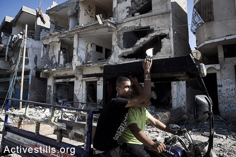 Palestinians passed by destroyed buildings in Shujaiyeh, a neighborhood in the east of Gaza City, during a ceasefire, July 27, 2014. During the ceasefire on 26 July, many Palestinians went back to Shujaiyeh to inspect the damages together with medics who attempted to rescue injured or collect bodies. Dozens of bodies were collected but many remain as Palestinians do not have all the necessary equipment to dig. Israeli attacks turned the neighborhood into a scene of utter devastation, with entire buildings flattened and thousands forced to flee.  Israeli attacks have killed more than 1,000 Palestinians and injured around 5,000 in the current offensive.