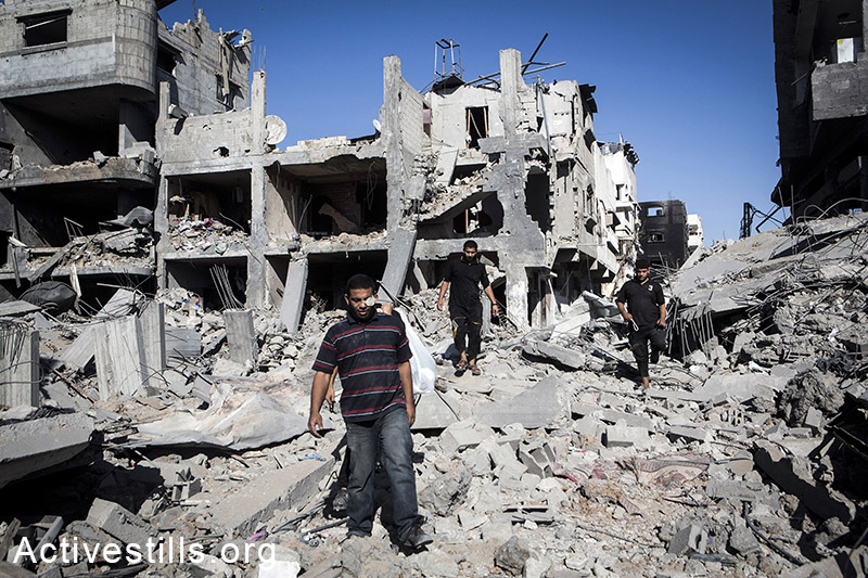 Palestinians walk through a destroyed quarter in Shujaiyeh neighborhood in the east of Gaza City, during a ceasefire, July 27, 2014. During the ceasefire on 26 July, many Palestinians went back to Shujaiyeh to inspect the damages together with medics who attempted to rescue injured or collect bodies. Dozens of bodies were collected but many remain as Palestinians do not have all the necessary equipment to dig. Israeli attacks turned the neighborhood into a scene of utter devastation, with entire buildings flattened and thousands forced to flee.  Israeli attacks have killed more than 1,000 Palestinians and injured around 5,000 in the current offensive.