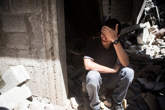 A Palestinian crying near rubbles of his home after the latest round of Israeli attacks against Al Shaja'ia, Gaza City, July 20, 2014.  (Anne Paq/Activestills.org)