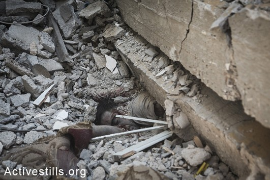 A Palestinian killed during the latest round of Israeli attacks against Al Shaja'ia is seen under the rubble of a house, Gaza City, July 20, 2014.  (Anne Paq/Activestills.org)
