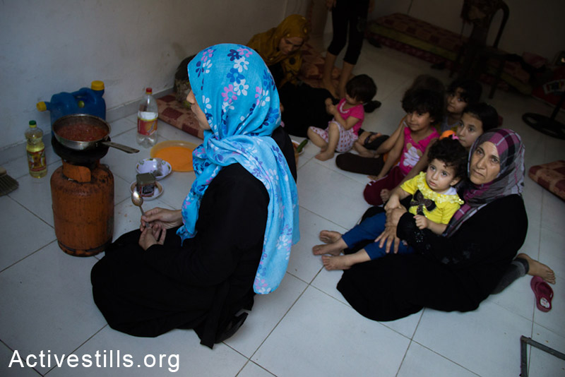 A Palestinian family had evacuated their house in Beit Hanoun after being warned by Israeli Occupation. Now the family lives in a store near to Kamal Edwan Hospital in Jabalya, July 24, 2014.  (Basel Yazouri/Activestills.org)
