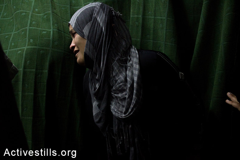 A woman mourns for her young child, killed by an Israeli airstrike over an UNRWA school in Beit Hanoun, July 24, 2014. (Anne Paq/Activestills.org)